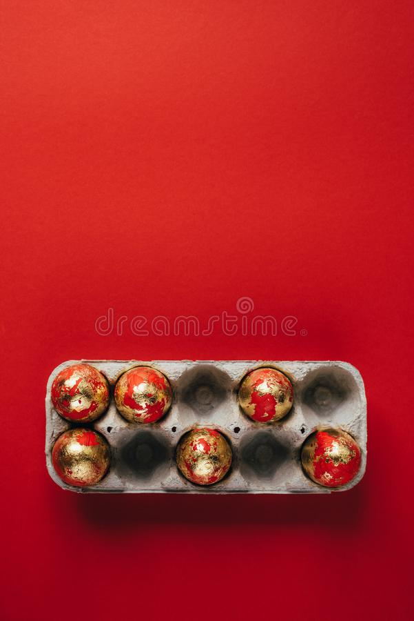 Группа в составе красные и золотом покрашенные пасхальные яйца в яйц-коробке картона стоковые фотографии rf