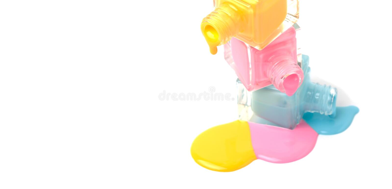 Группа в составе 3 красочных бутылки маникюра на разлитой краске стоковое фото