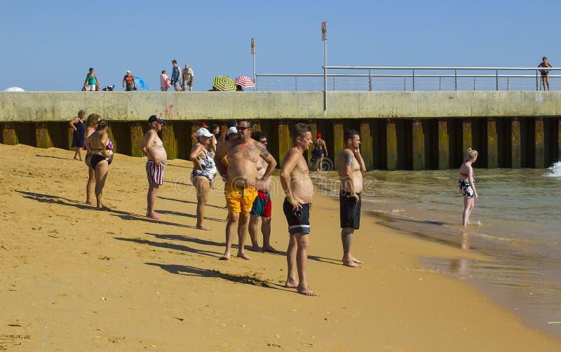 Группа в составе люди и женщины с большим пристальным взглядом животов вне к морю от пляжа на старом городке в Albuferia в Португ стоковая фотография