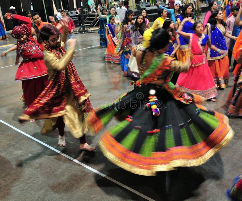 Группа в составе люди и женщины танцуют в действии Наслаждающся индусским фестивалем носить Navratri Garba традиционный уничтожьт стоковые изображения