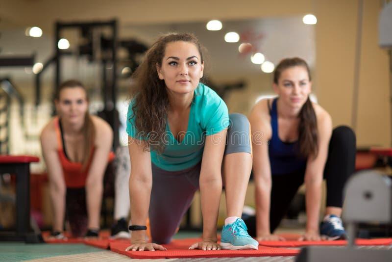 Группа в составе маленькие девочки делая тренировки в спортзале стоковое фото