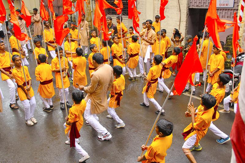 Группа в составе малые мальчики, танцуя с флагами, во время шествия Ganapti, фестиваль Ganapati стоковые изображения