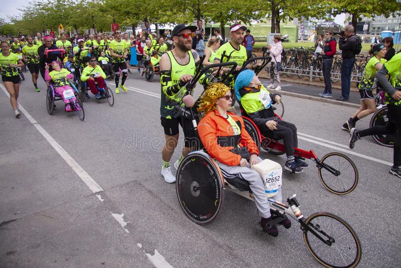 Группа в составе марафонцы нажимая бежать кресло-каталки с неработающими людьми помогая им для того чтобы выполнить бег стоковые изображения
