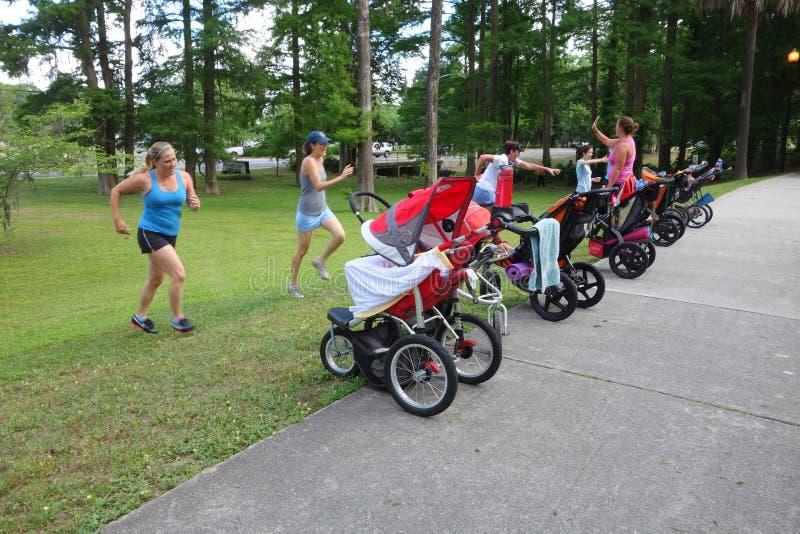 Группа в составе матери бежать с прогулочными колясками в парке. стоковые фото