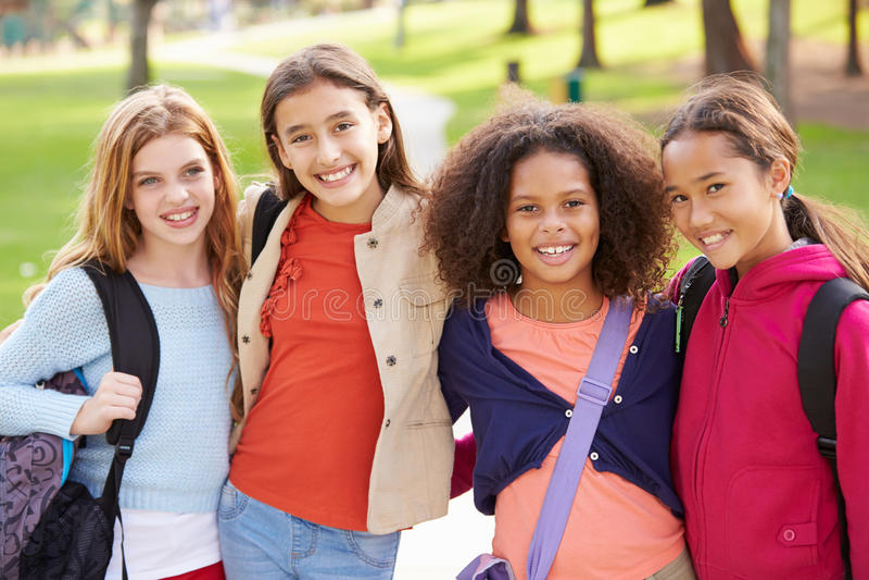 Группа в составе маленькие девочки вися вне в парке совместно стоковые фотографии rf