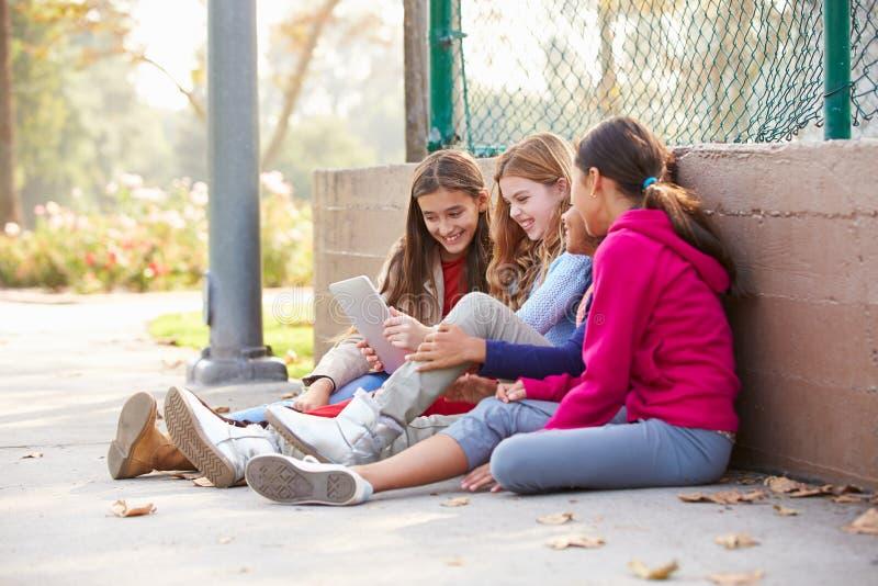 Группа в составе маленькие девочки используя таблетку цифров в парке стоковые изображения rf