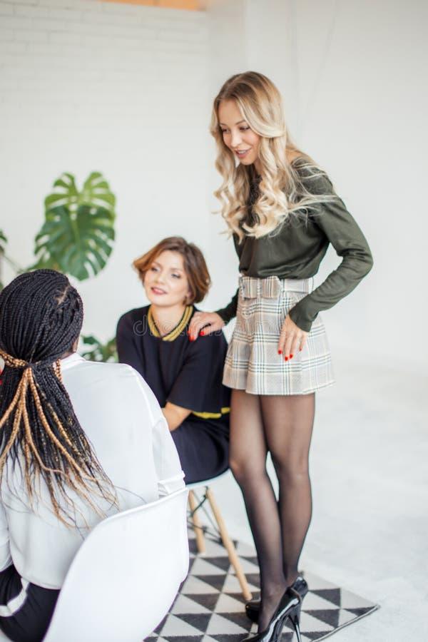 Группа в составе многонациональная женская команда работая в офисе стоковое изображение