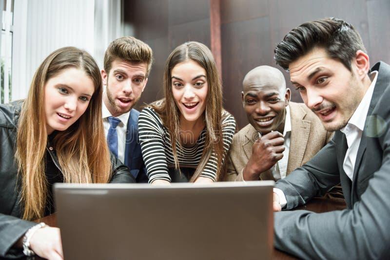 Группа в составе многонациональные занятые люди смотря компьтер-книжку стоковое изображение rf