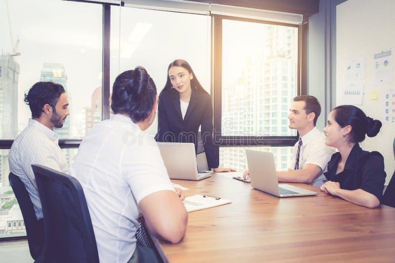 Группа в составе молодая команда дела с встречей руководителя менеджера женщины стоящей в конференц-зале стоковые изображения