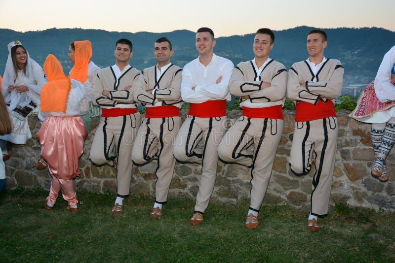 Группа в составе молодой человек нося традиционный представлять обмундирования стоковое фото