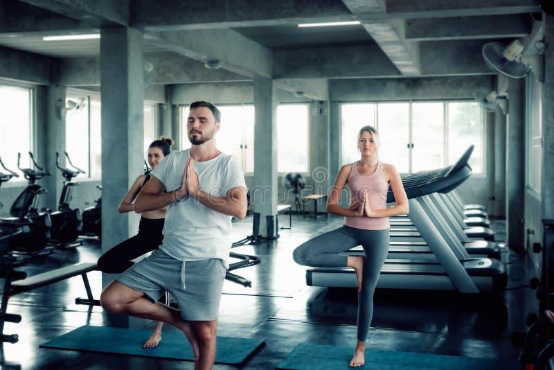 Группа в составе молодой Sporty Yogi практикует йогу с инструктором в спортзале , Sporty люди в Sportswear разрабатывают тренируя стоковая фотография