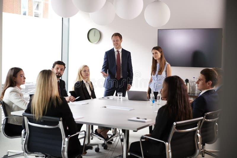 Группа в составе молодые бизнесмены и коммерсантки встречая вокруг таблицы на постдипломном дне оценки рекрутства стоковая фотография rf
