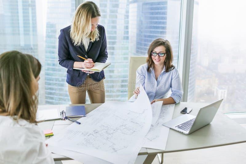 Группа в составе молодые бизнес-леди работая в современном офисе стоковые фото