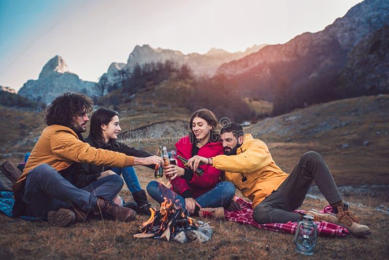Группа в составе молодые друзья вокруг огня лагеря стоковое фото
