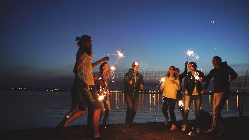 Группа в составе молодые друзья имея партию пляжа Друзья танцуя и празднуя с бенгальскими огнями в twilight заходе солнца стоковые изображения rf