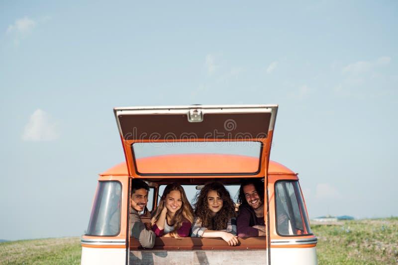 Группа в составе молодые друзья на roadtrip через сельскую местность, смотря из окна стоковое изображение
