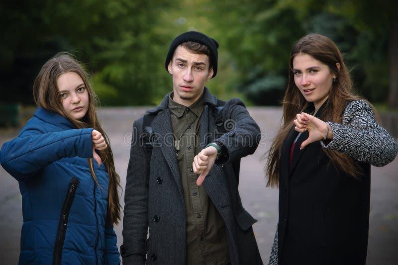 Группа в составе молодые друзья показывая большой палец руки вниз стоковые изображения