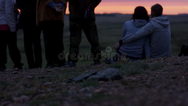 Группа в составе молодые друзья стоя совместно и смотря заход солнца Вид сзади молодые люди восхищая взгляд белизна группы калибр стоковые фото
