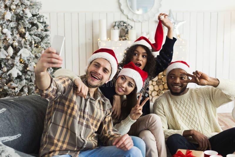 Группа в составе молодые друзья в шляпах Санта принимая selfie стоковое изображение rf