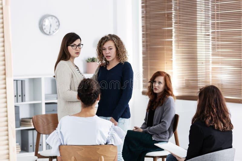 Группа в составе молодые женщины говоря усаживание в круге Психологическая концепция поддержки стоковые фотографии rf