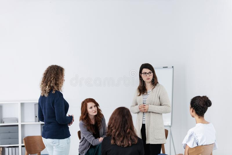 Группа в составе молодые женщины говоря усаживание в круге Психологическая концепция поддержки стоковая фотография rf