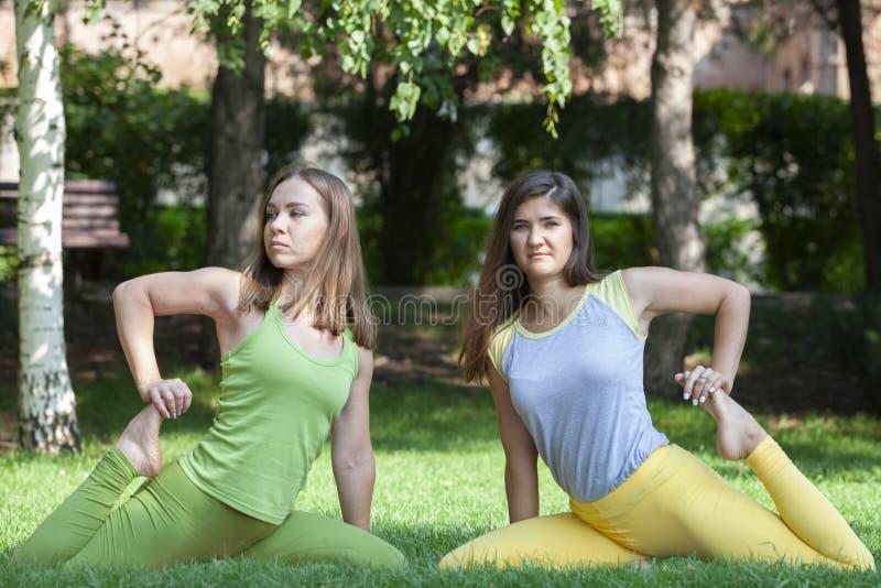 Группа в составе молодые женщины делая йогу в парке стоковая фотография rf