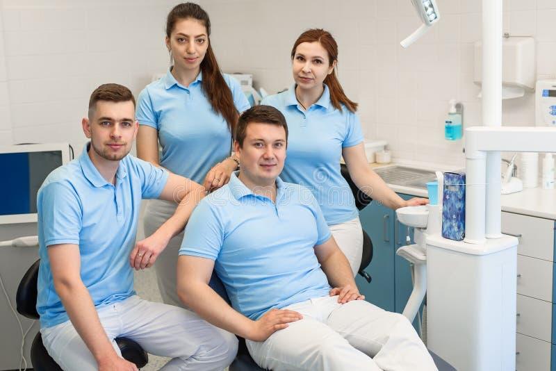 Группа в составе молодые и счастливые зубоврачебные доктора стоит около одина другого на зубоврачебной клинике Концепция сыгранно стоковое фото rf