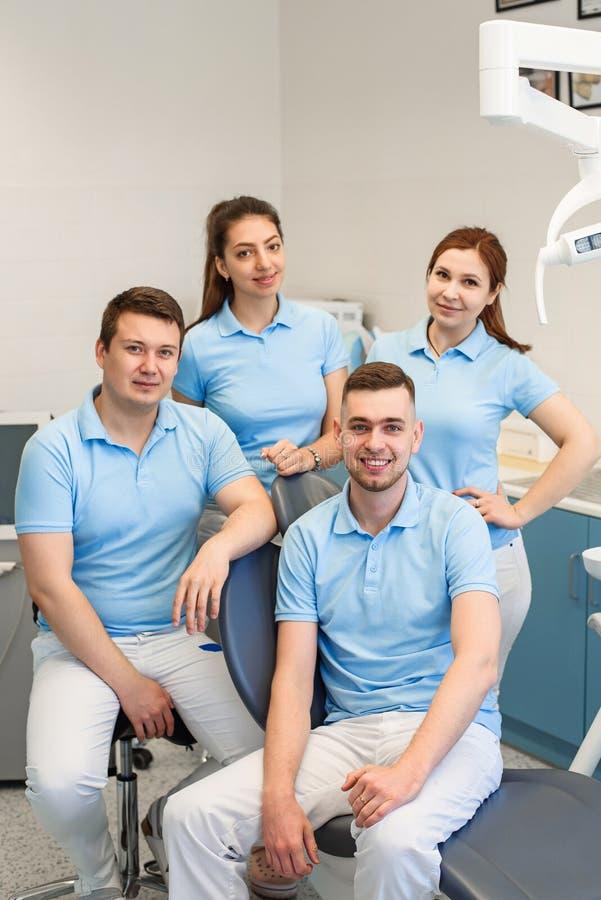 Группа в составе молодые и счастливые зубоврачебные доктора стоит около одина другого на зубоврачебной клинике Концепция сыгранно стоковые изображения rf