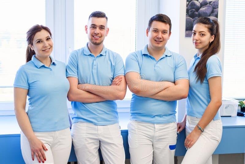 Группа в составе молодые и счастливые зубоврачебные доктора стоит около одина другого на зубоврачебной клинике Концепция сыгранно стоковое фото