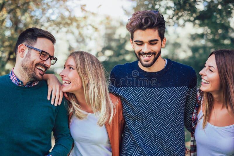 Группа в составе молодые люди идя через парк стоковое изображение