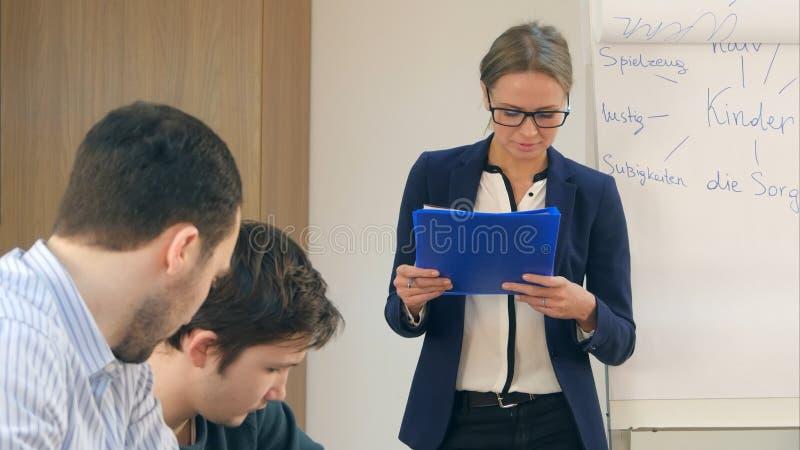 Группа в составе молодые люди изучая в университете сидя в аудитории во время лекции стоковое фото