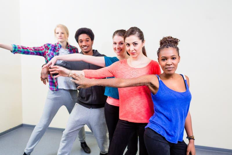 Группа в составе молодые люди имея уроки танца стоковая фотография rf