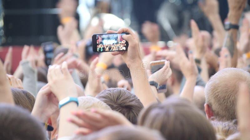 Группа в составе молодые люди наслаждаясь внешним музыкальным фестивалем Вид сзади конца-вверх толпы на концерте Смешные люди сни стоковое фото rf