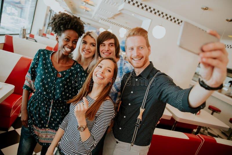 Группа в составе молодые люди принимая selfie с мобильным телефоном стоковое фото