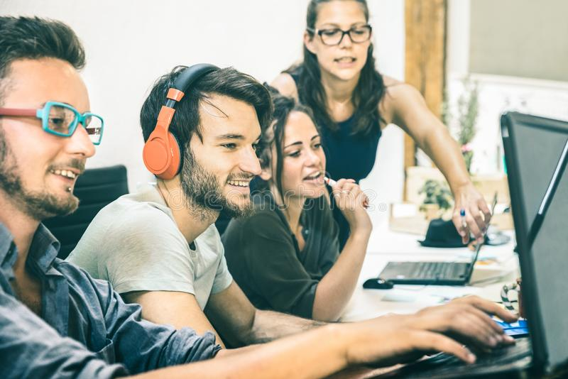 Группа в составе молодые люди работая с компьютером в startup офисе стоковые изображения rf