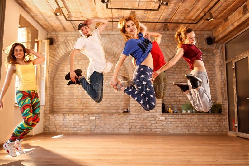 Группа в составе молодые люди скача совместно стоковые изображения rf