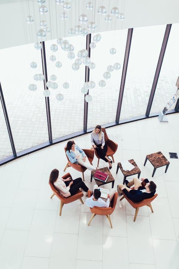 Группа в составе молодые профессионалы дела сидя совместно и имея случайный обсуждать в прихожей офиса достигая целей стоковое изображение rf