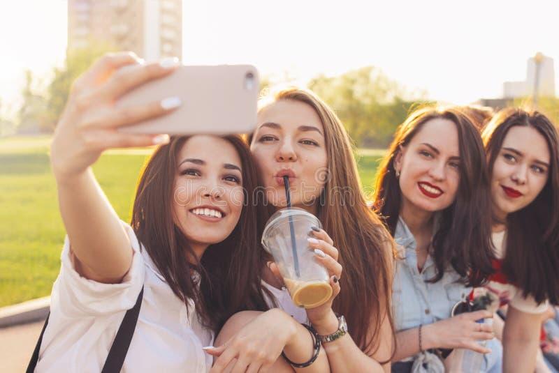 Группа в составе молодые счастливые беспечальные подруги делая selfie на улице города лета, предпосылке времени захода солнца стоковые изображения rf