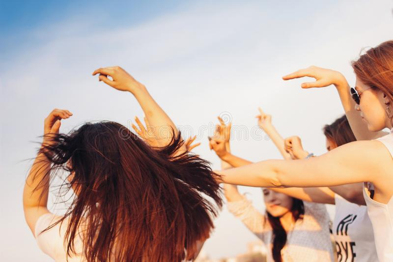 Группа в составе молодые счастливые танцы загорает девушек на предпосылке голубого неба, лете, под открытым небом партии стоковые фото
