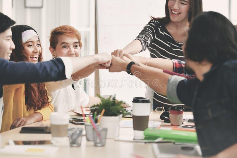 Группа в составе молодые businesspersons кулак-bumping в согласовании в встрече стоковое фото rf
