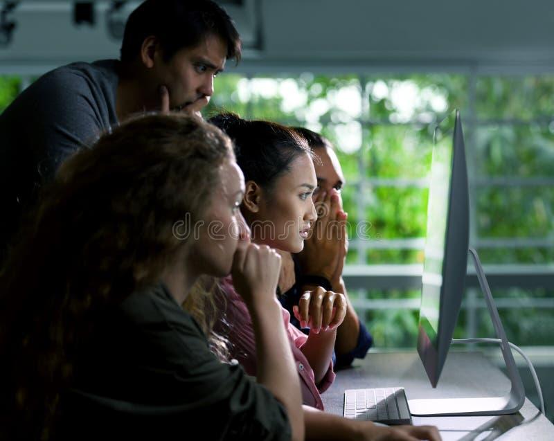 Группа в составе молодые businesspersons смотря умышленно на экране стоковые фотографии rf