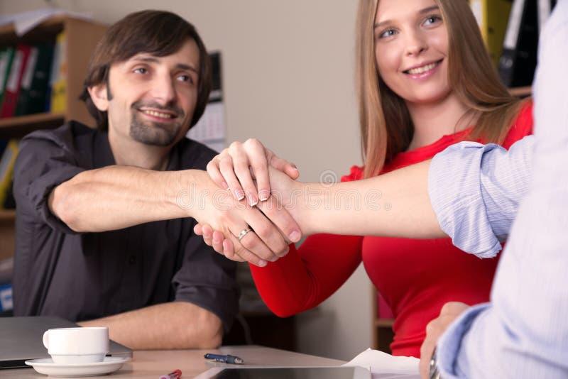 Группа в составе молодые бизнесмены тряся руки стоковое изображение rf