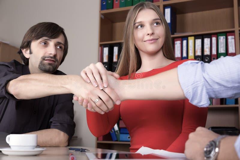 Группа в составе молодые бизнесмены тряся руки стоковые изображения rf