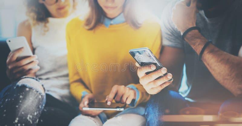 Группа в составе молодые битники сидя на софе держа руки en и используя электронные устройства Концепция сыгранности Coworking стоковые изображения rf