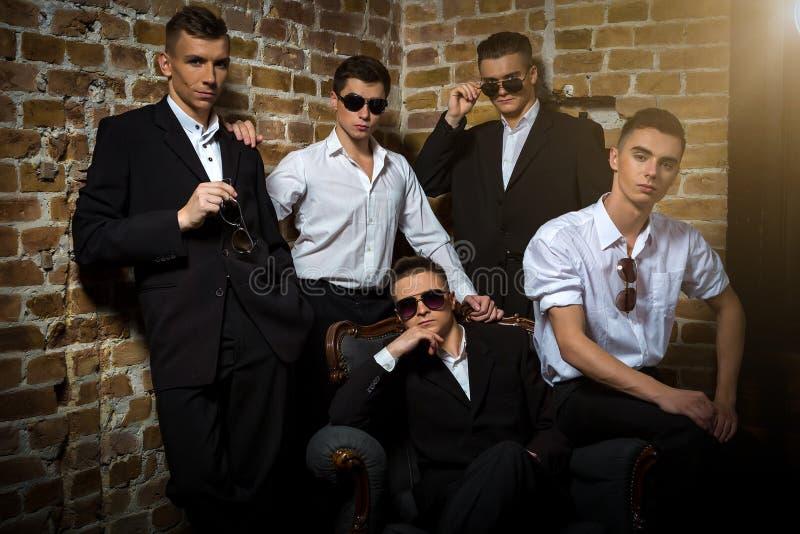 Группа в составе молодые красивые сексуальные мальчики представляя против кирпичной стены и Windows стоковые изображения rf