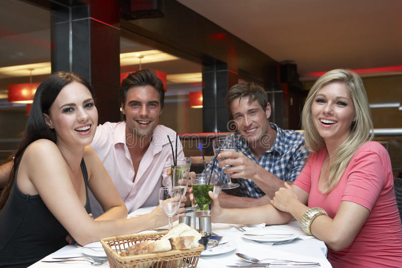 Группа в составе молодые друзья наслаждаясь едой в ресторане стоковые фото