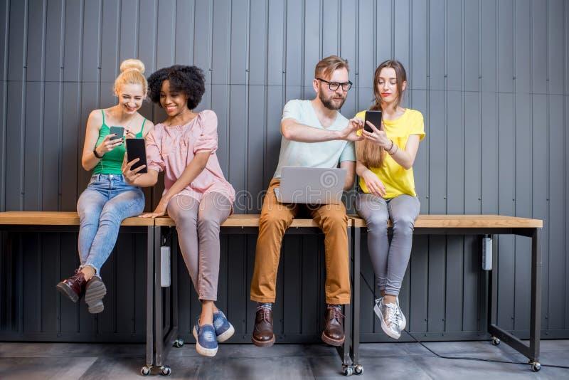 Группа в составе молодые люди с устройствами внутри помещения стоковое фото rf