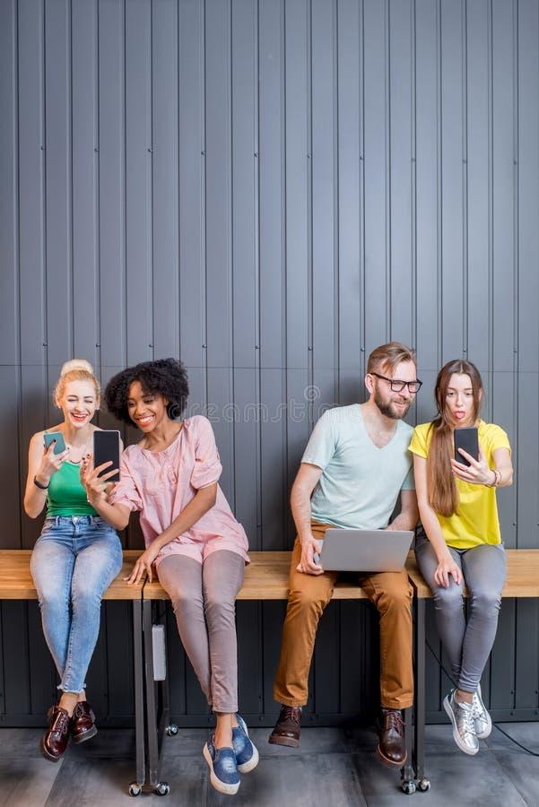 Группа в составе молодые люди с устройствами внутри помещения стоковая фотография rf