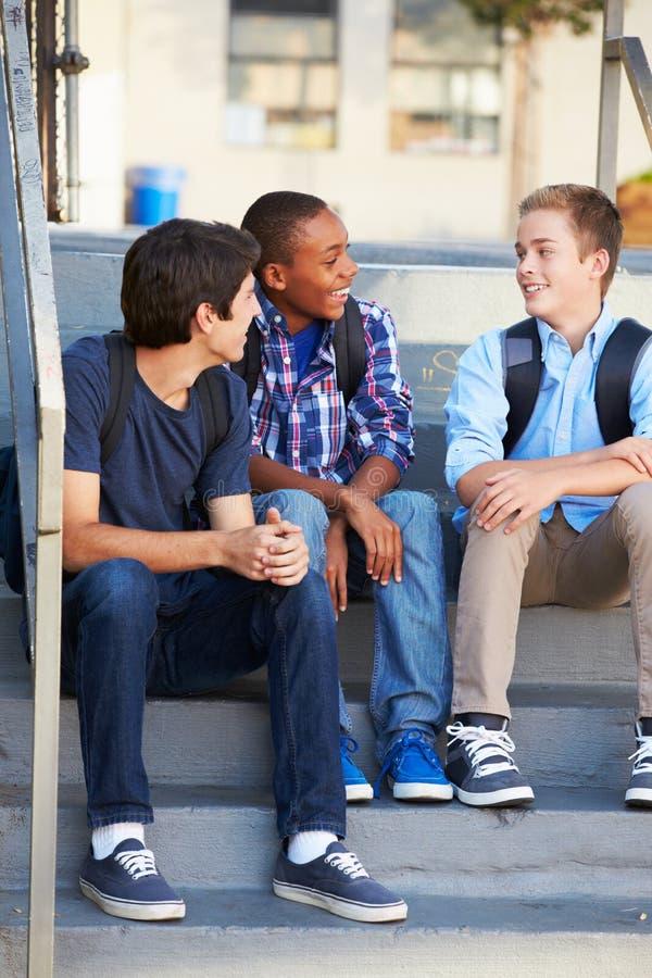 Группа в составе мужские подростковые зрачки вне класса стоковые изображения