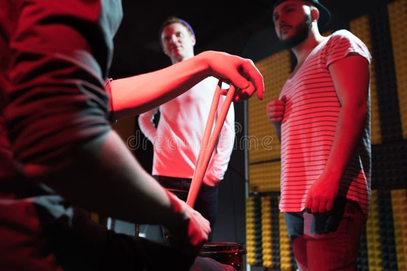 Группа в составе музыканты обсуждая песню стоковые изображения